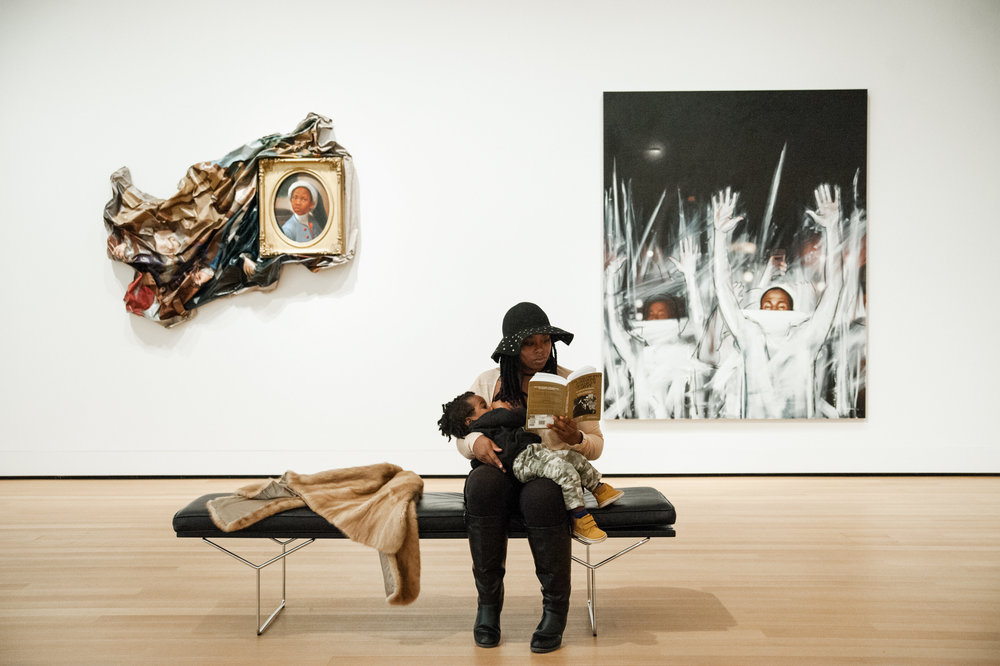"Amelia Sherwood, ""being brave breastfeeding"" in public, while reading in front of art by  Titus Kaphar . Photo credit  Rachel Liu"