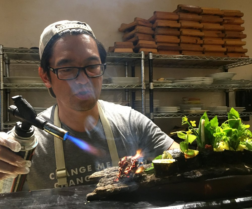 "Chef Bun Lai of Miya's Sushi in New Haven, CT burns mugwort to connect with indigenous cultures many of which us this ""weed"" to enhance spiritual experiences and dreams - on this sushi roll platter of wild foraged weeds and sustainable seafood."