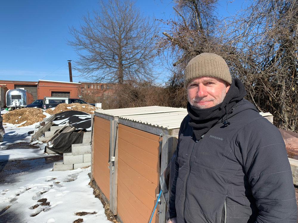 """Domingo Medina, owner of Peels & Wheels Composting stands by some of his solar powered compost bins, contributing to """"a corner of sustainability"""" transforming an asphalt parking lot he shares with Phoenix Press and New Haven Farms under interstate 95 in New Haven, CT."""