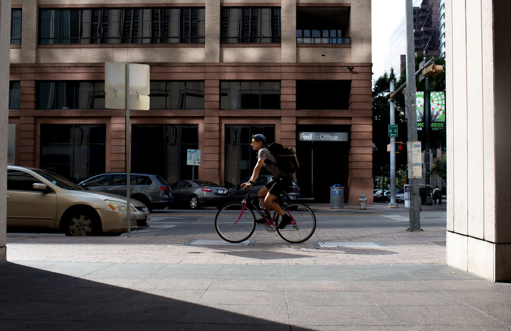Johnpaul doesn't wear a helmet while he works, but says he bikes more cautiously than other bike couriers. He thinks couriers who run lights and stop signs are sending a bad message to drivers downtown. Austin, TX, November 10, 2016.
