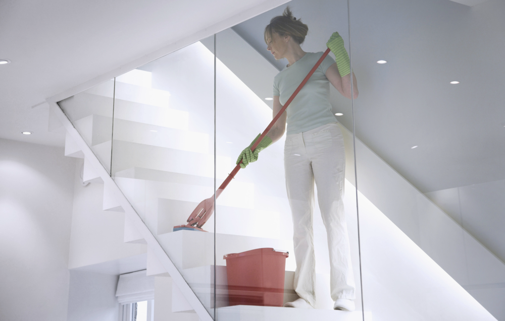 A woman cleans the stairs of an office