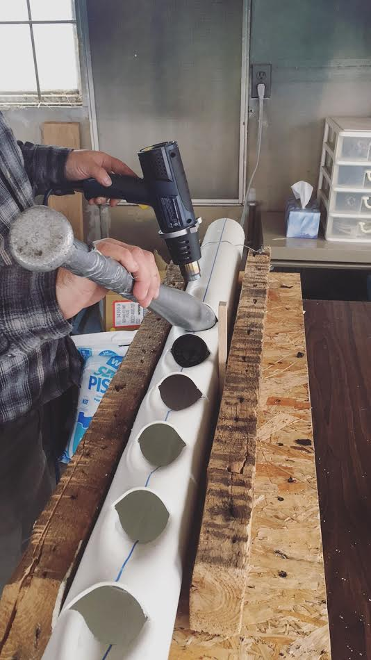 The making of the PVC pipe: A heater, a home-made wooden base, an aluminium baseball bat and some cold water to cool the baseball bat between each hole process.