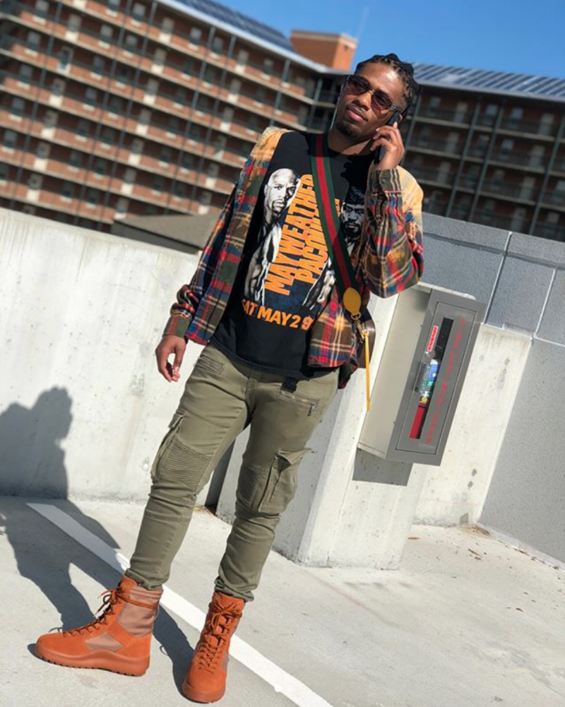 "Charles Royals  is wearing  Yeezy Season 3  Burnt Sienna Military Boots,  Embellish  Ghost Cargo Biker Denim ""Olive"" pants, a vintage Mayweather vs. Pacquiao tee, a thrifted flannel,  Jean Paul Gaultier  56-3281 ""Forks"" frames, and a  Gucci  GG Supreme Messenger Bag."