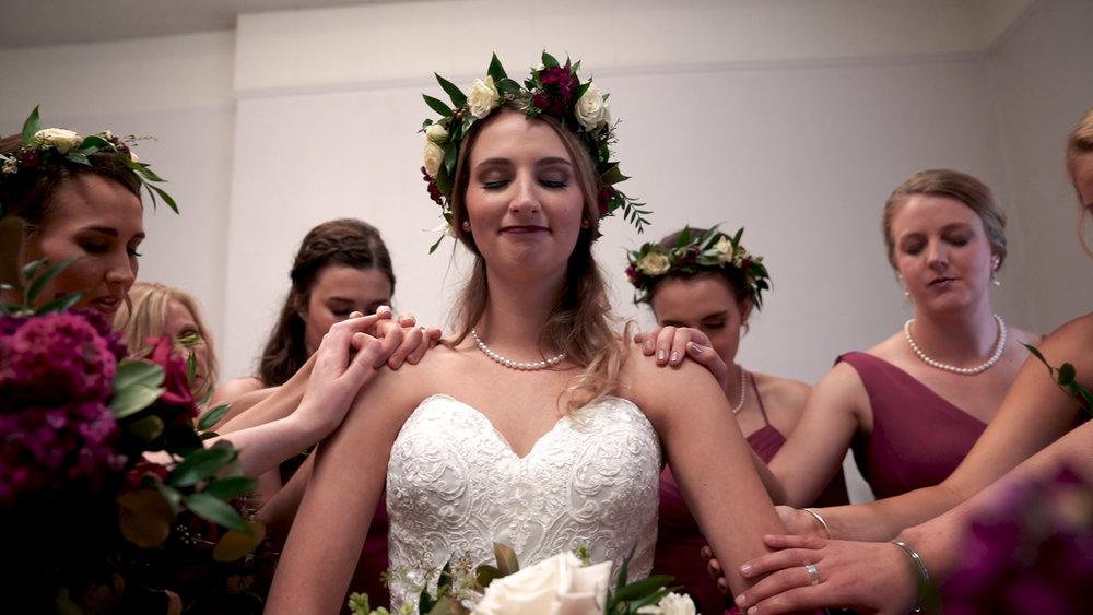 bride praying with bridesmaids before wedding