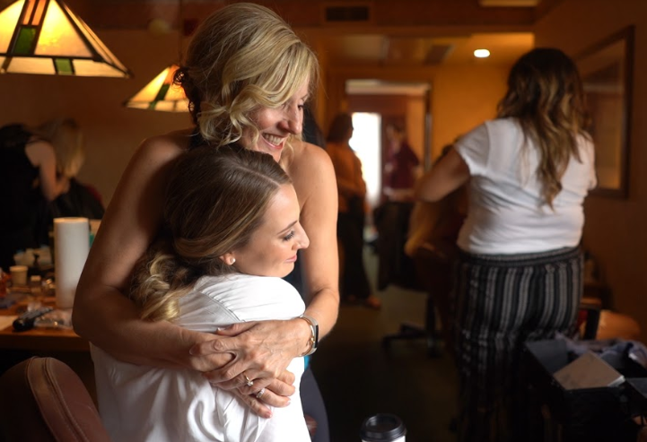 mother of the bride hugging bride while getting ready for wedding day