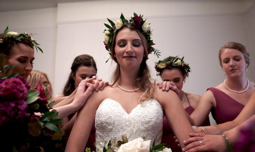 bride with bridesmaids praying