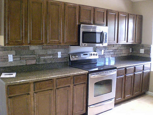 The rustic beauty of this backsplash pulls the cabinets and counters together in a natural way.