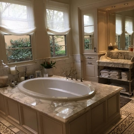 Quartz shevling matches this elegant tub surround.