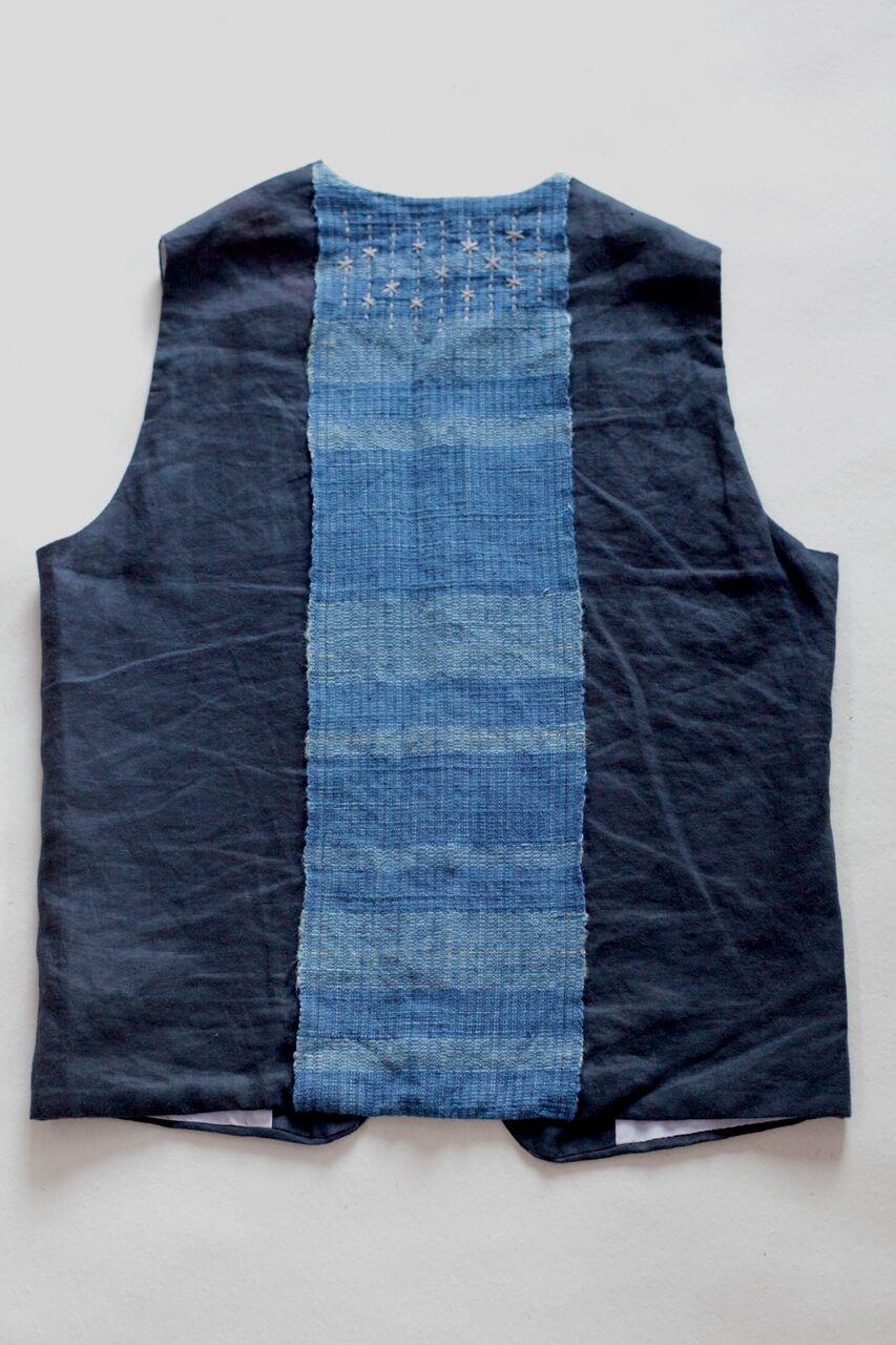 ◎島海ベスト  Made in Japan  表:麻-100% , 帯:綿麻100%  竹素材のボタン。背中の帯の部分は淡路島のいついろさんと麻と綿糸を使い淡路島産の藍染、玉ねぎで染め創り上げた手織物を使用。帯のカラーリングは瀬戸内海の海の色を、麻炭で染めた糸で刺し子刺繍は星空をイメージしました。いろんな作業するひとの背中が物語ります。  本体価格¥20,000 + tax 背中の背守りになる刺繍はオプションになります。¥3,000+ tax    お問合わせはこちらからお願いします。