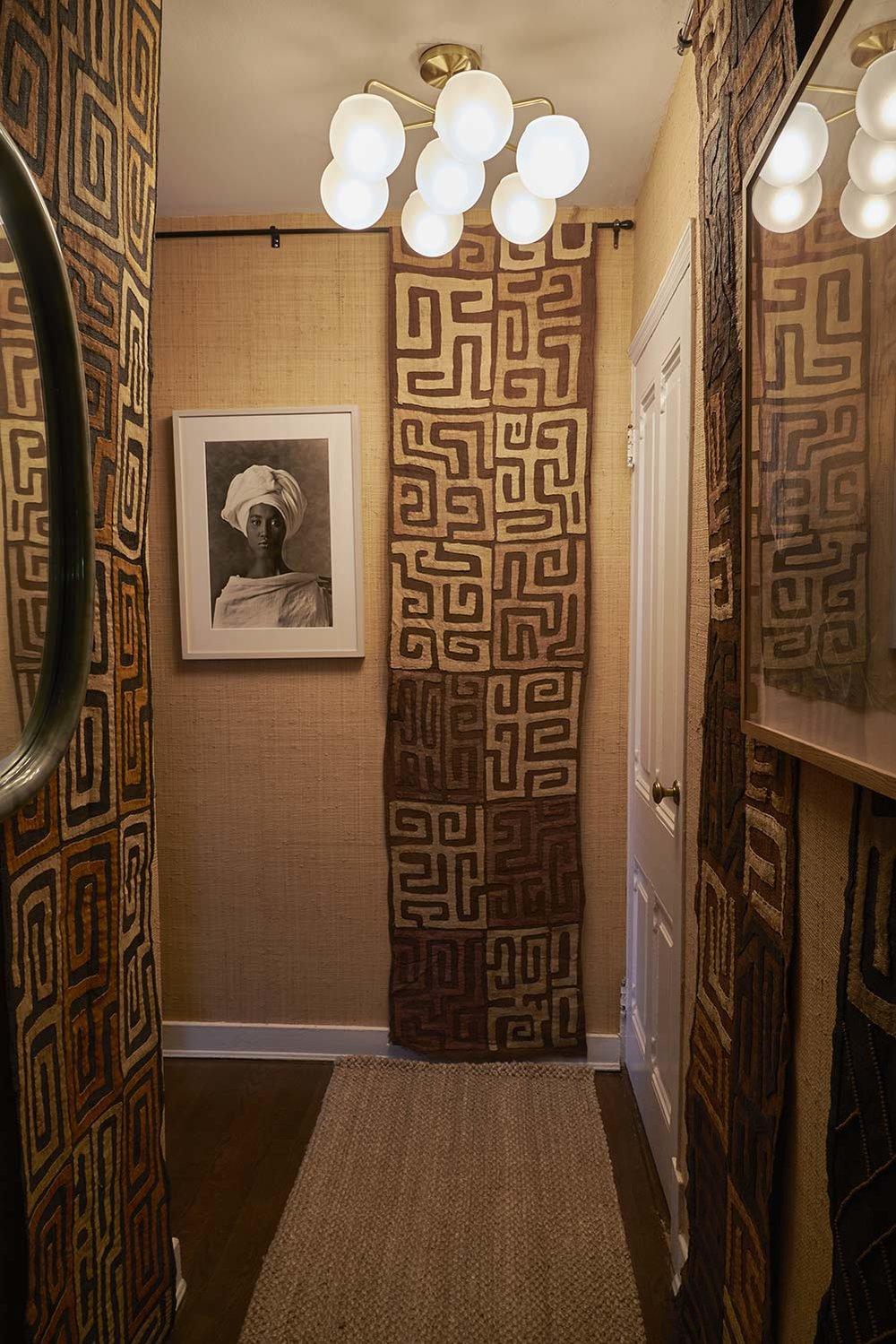 Upper East Side | New York   Une petite entrée inspirée de l'Afrique avec des tapis Kuba du Mali et des murs tapissés en raphia nous conduit dans une grande pièce aux couleurs vieux rose et lilas dont l'ambiance italienne des années 50 est accentuée par des photographies en noir et blanc, des meubles en laque et des lampes vintage.