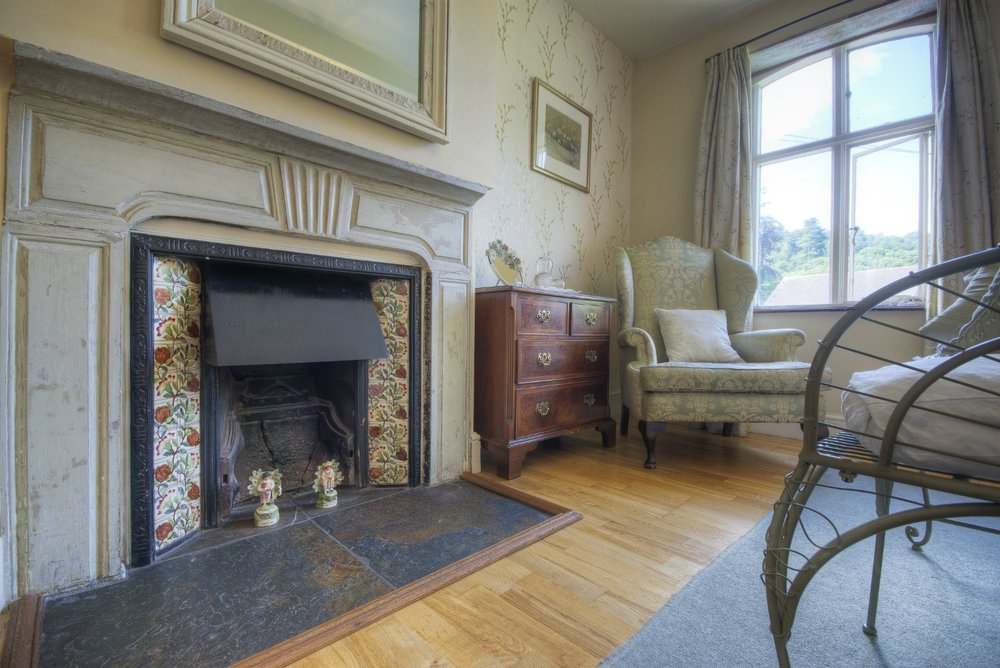 Bedroom fireplace, elegant furniture and period window