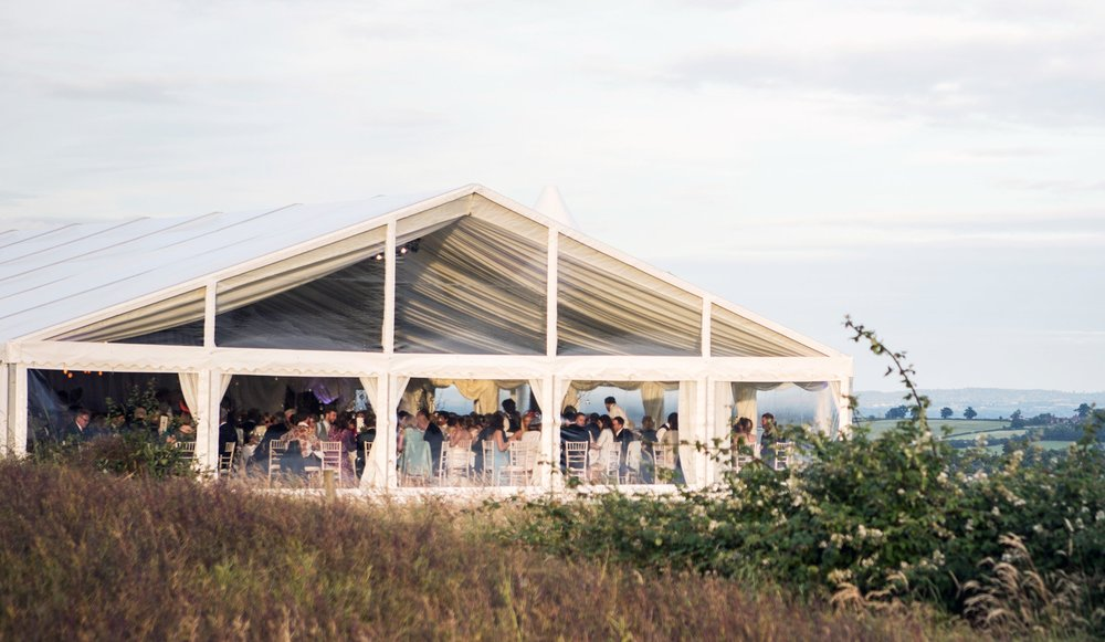 the brief. - Joseph Benjamin Marquees were approached by the Hamilton-Ely family to create something special for their daughter's wedding. The elevation of the farm created a fantastic backdrop, and with the clients keen to involve this, we nestled the marquee into the hillside above.We utilised our cassette flooring system to level the site and constructed a 12mx6m decking porch entrance with a feature staircase, which allowed the guests an unrivalled view. The clients loved the veranda so much that they decided to give their speeches from there. Clear PVC around the dining area enabled guests to appreciate the view throughout the day and allowed plenty of natural light to pass through the marquee.