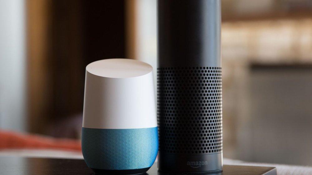 Google Home standing next to Amazon Echo