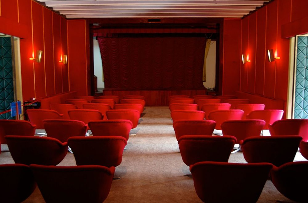 Here the cinema is seen with different seating arrangement and carpet.