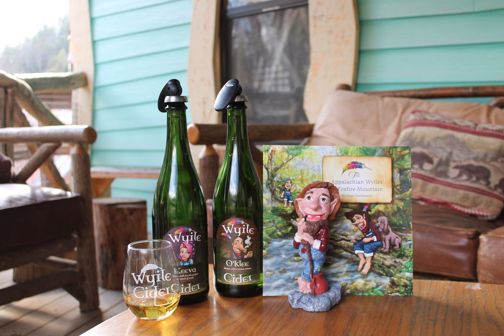 Cider bottles, tasting glasses, children's book and mascot