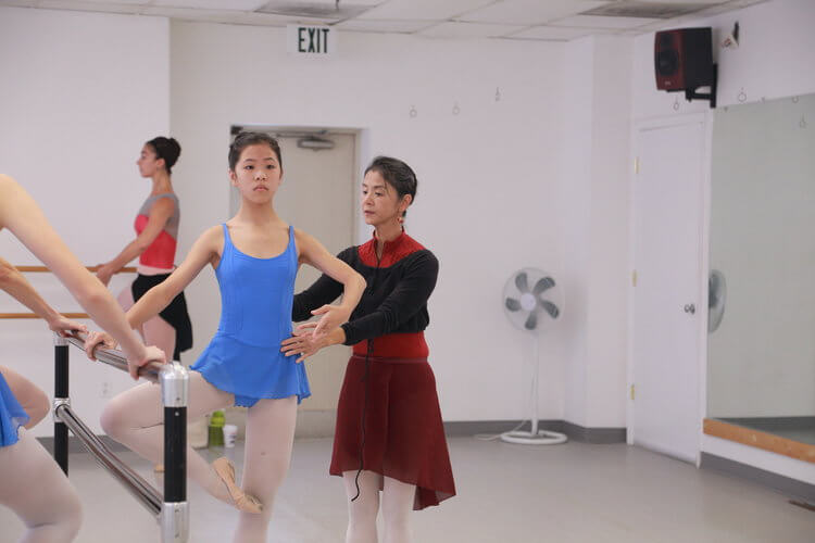 Ms. Misako teaches a student in her ballet class.