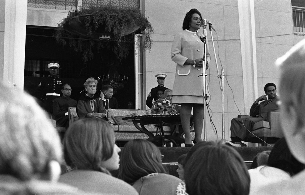 Coretta Scott King speaks to students from the U.S. embassy school in New Delhi, India, January 1969. Civil Rights activist Andrew Young is at far right. Photo by Tim Brown.