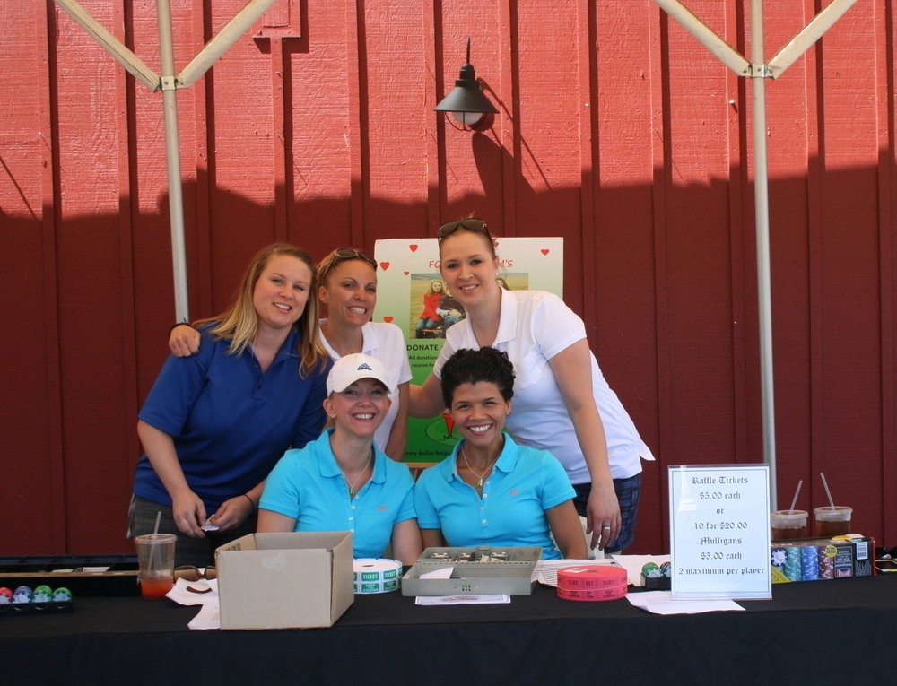 Volunteers register players at the annual Guten Foods Golf Tournament at Langdon Farms Golf Club to raise money for Zenger Farm and New City Initiative.