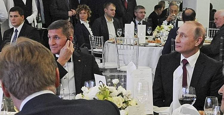 Flynn sits at the right hand of Vladomir Putin during an RT gala for which Michael Flynn was paid tens of thousands of dollars.