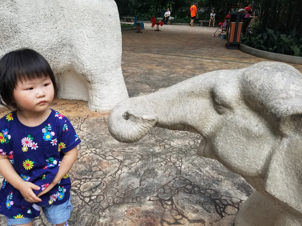 Playing with the elephant statues in the park!