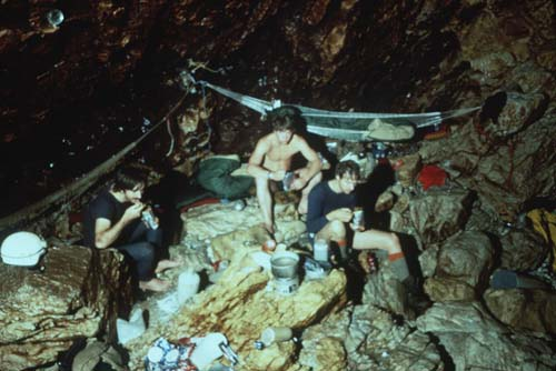 Spartan Outpost: Left to Right: Bob Jefferys, Rob Parker, and Noel Sloan work on a humble meal of freeze dried food at Camp 2, 4.2 kilometers from the entrance and beyond six sumps comprising a kilometer of underwater travel. Camp 2 was occupied for 7 days during the 1984 expedition. [photo �1984 Bill Stone]