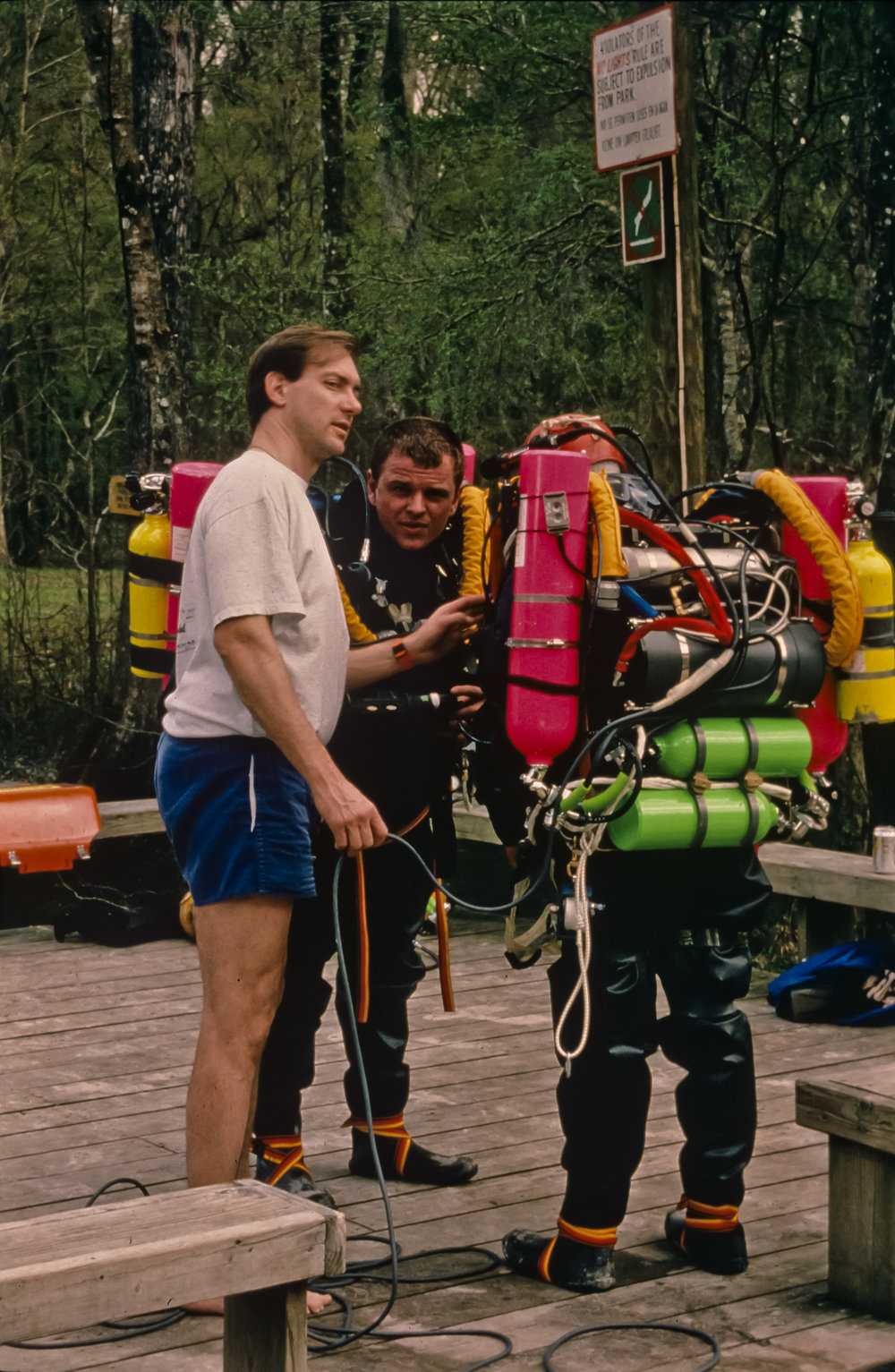 Noel Sloan discusses a dive plan with Ian Rolland and Kenny Broad (back to camera) on the deck at Devil's Eye spring during rehearsal dives for the 1994 San Agustin expedition. Photo by U. S. Deep Caving Team/Bill Stone.