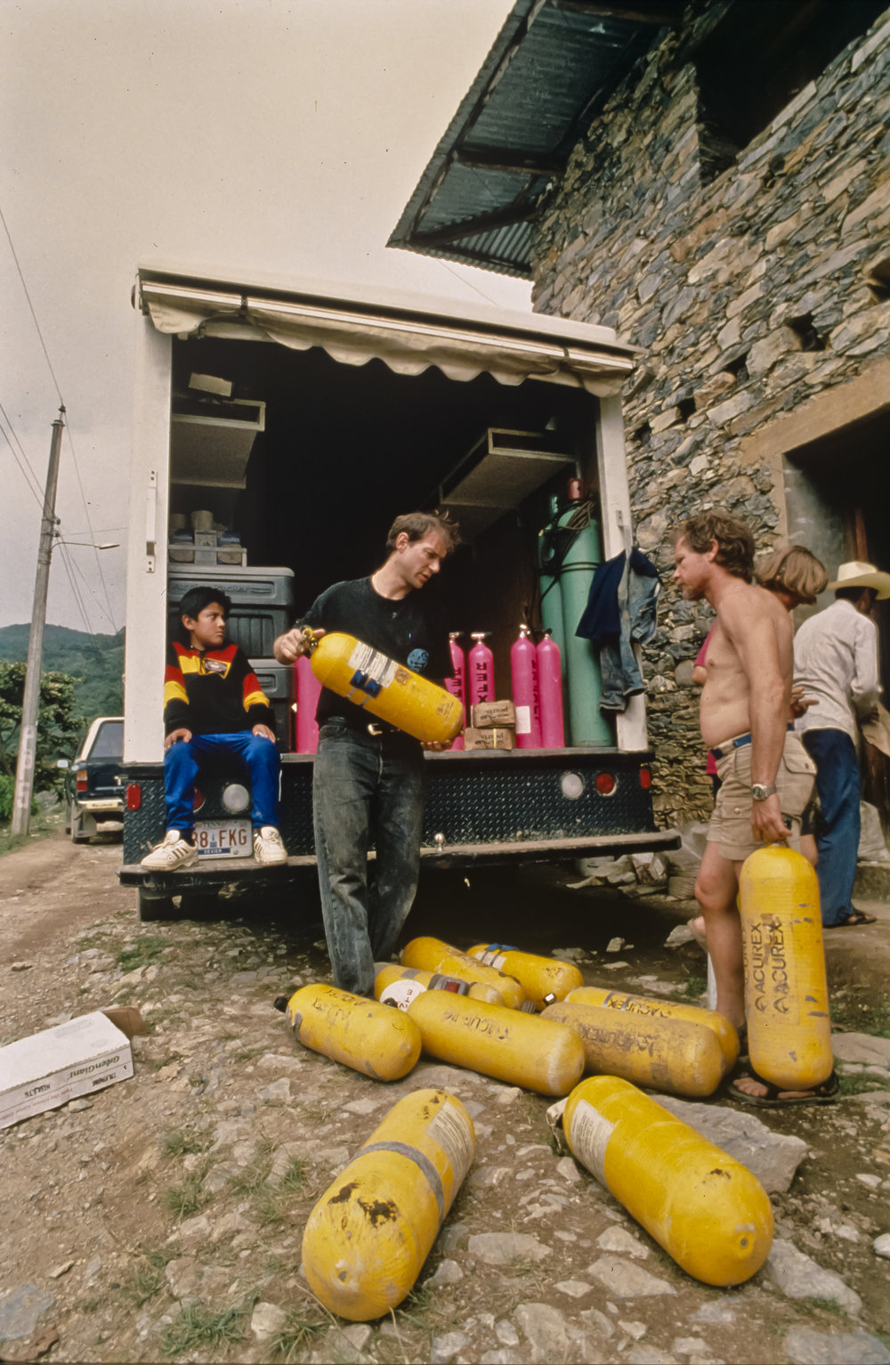 Arrival: Noel Sloan and Don Broussard unload dive cylinders at the house of Epifanio Villega. Photo by U. S. Deep Caving Team/Bill Stone.