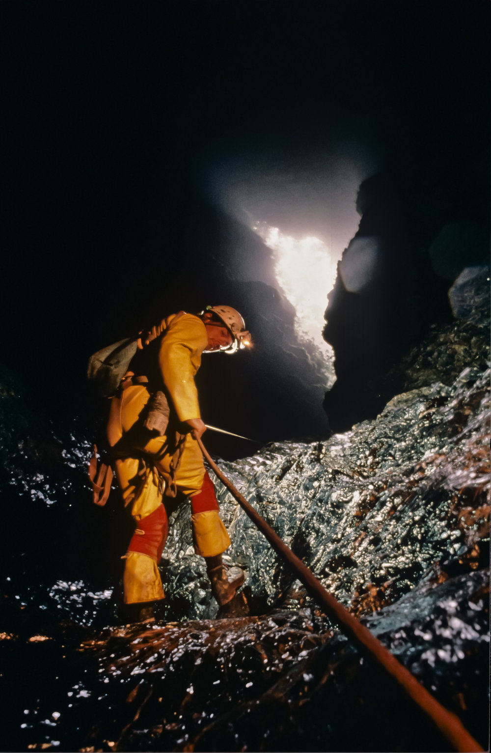 "Jim Brown completes the descent of the ""slip and slide"" pitch. At 120m vertically below the surface the last bit of daylight is visible before beginning the long trip down. Photo by U. S. Deep Caving Team/Wes Skiles."