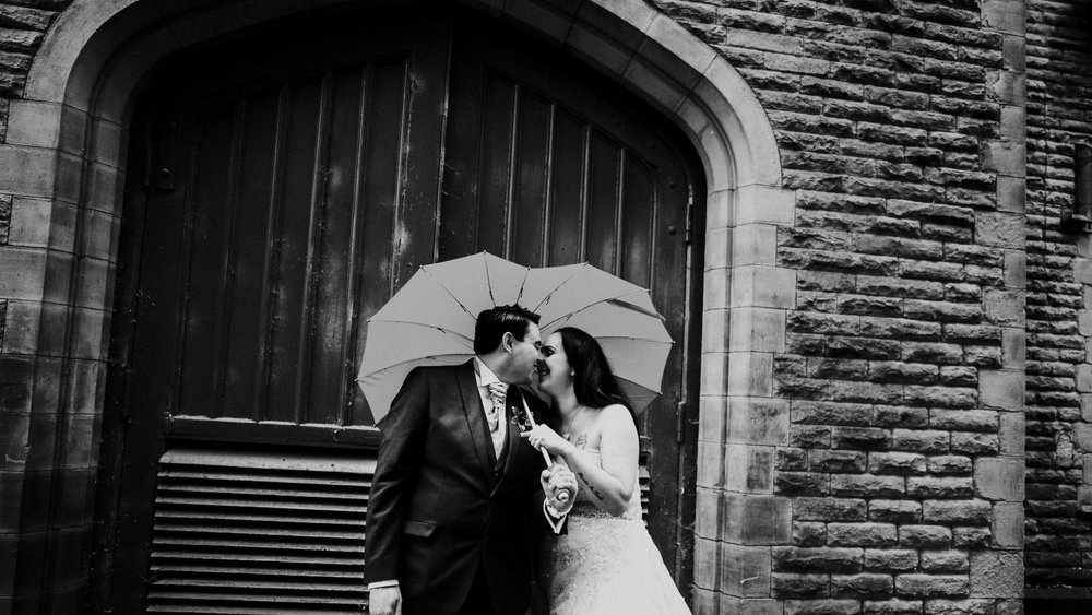 dramtic alternative winter wedding image of bride and groom kissing under heart umbrella in manchester