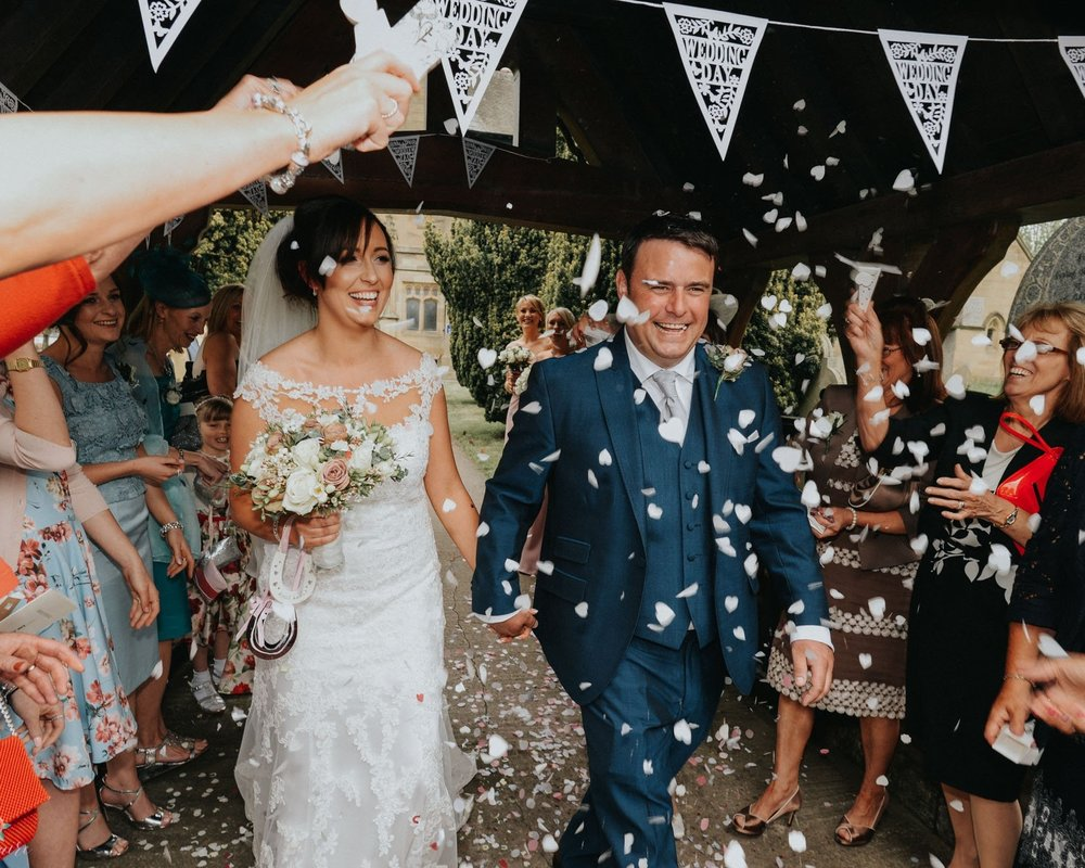 bride and groom walk through lots of confetti being thrown for their vintage wedding in north wales - north west wedding photographer