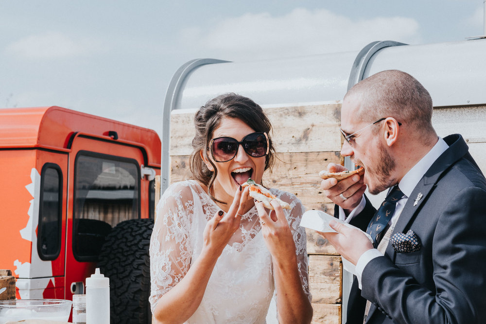 north wales wedding photography capturing bride and groom eating pizza at their alternative wedding.
