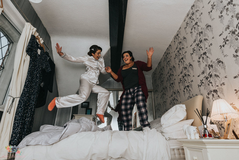 fun wedding photography by jade maguire photography in chester, bride and bridesmaid bouncing on bed having fun.