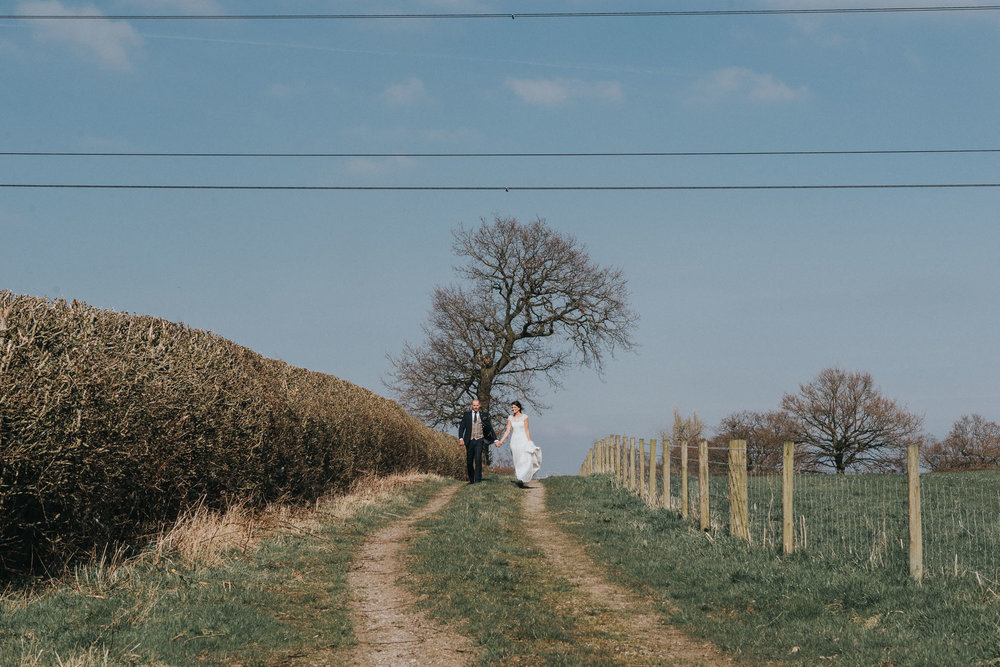 bride and groom walking hand in hand for their rustic farm wedding photography