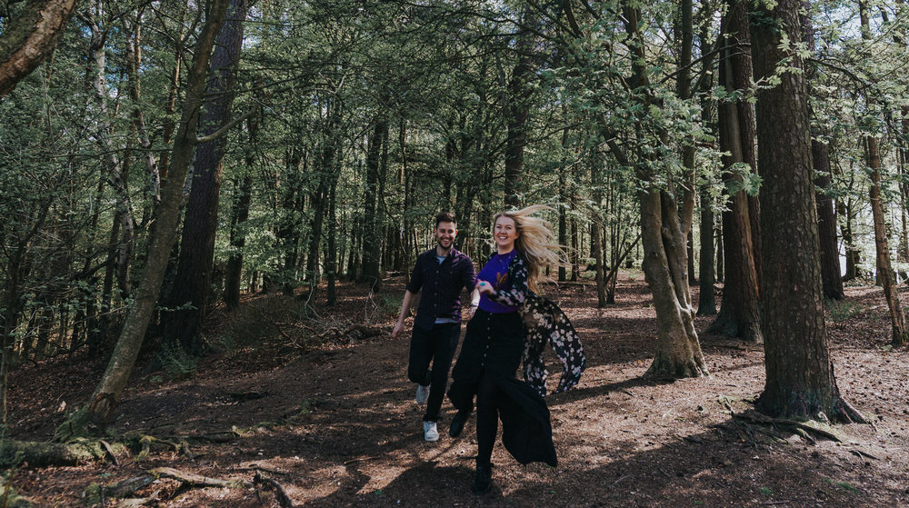 bride and groom running through woods for alternative wedding photography