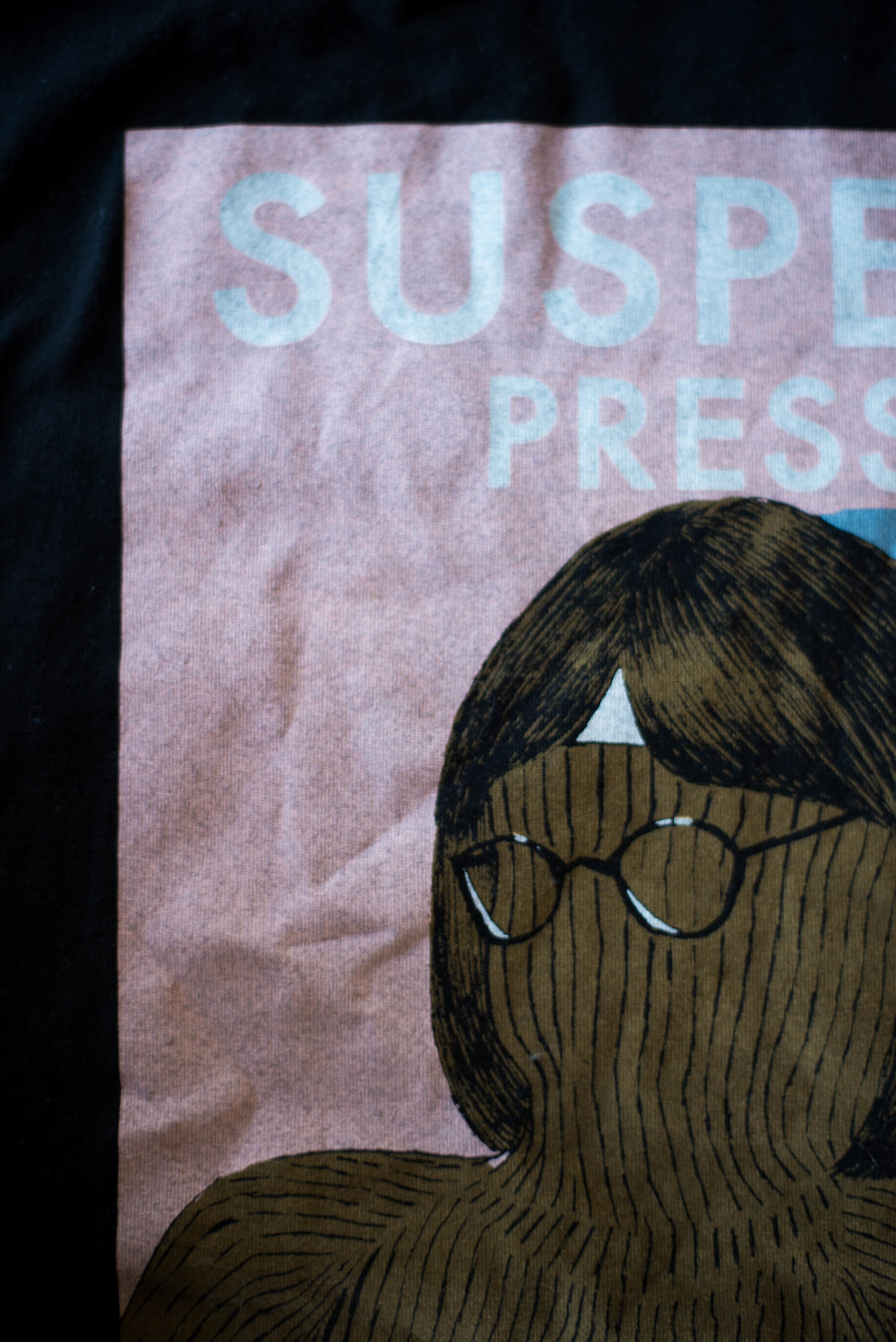Suspect Press. Print method VINTAGE. Screen printed on a Next Level shirt. Printed by A Small Print Shop.