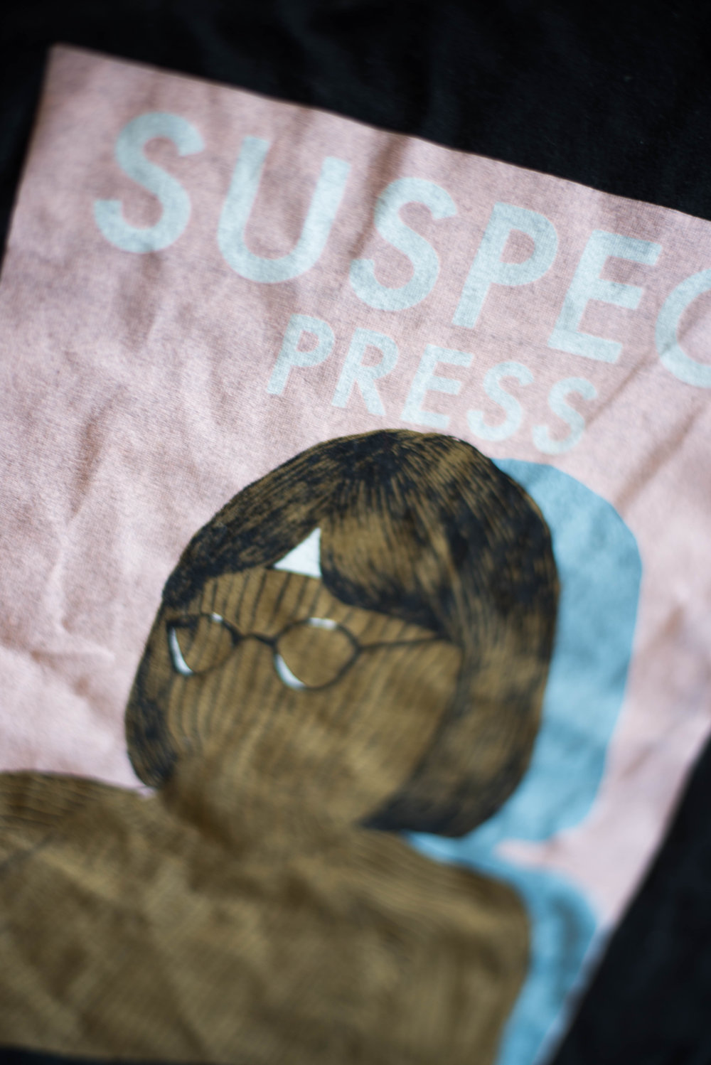 Suspect Press. Print method SOFT. Screen printed on a Next Level shirt. Printed by A Small Print Shop.