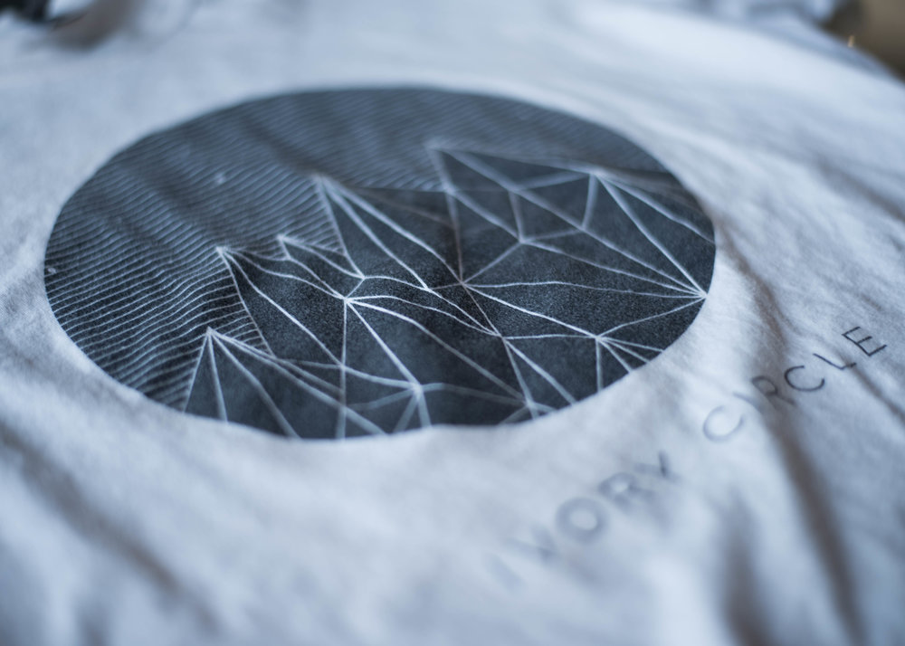 Ivory Circle. Print method VINTAGE. Screen printed on a Next Level shirt. Printed by A Small Print Shop.