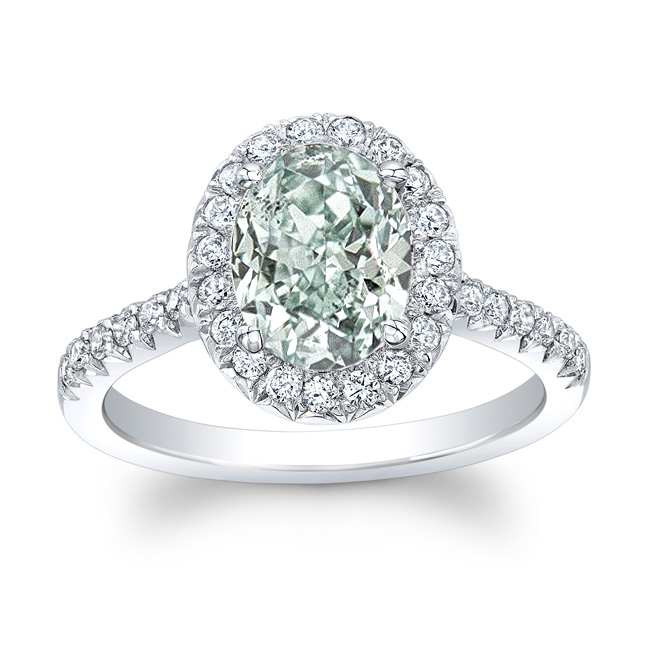 SEAFOAM  natural fancy green oval cut diamond set in a platinum halo setting with french pave set accent diamonds. This tradition halo design is meant to display the center diamond's extremely rare and natural green hue.