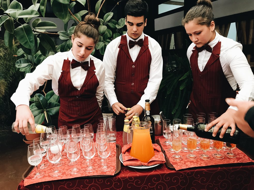 Hotel management students serve drinks for attendees