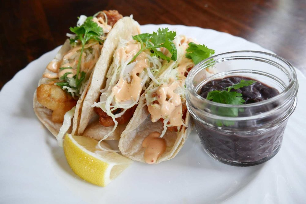 Crispy fish tacos with organic Mi Tierra tortillas, cilantro slaw and chipotle aioli, served with a side of black beans