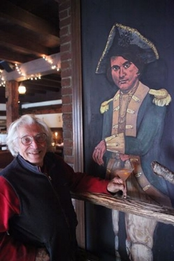 David Rothstein stands with the portrait of Captain Daniel Shays