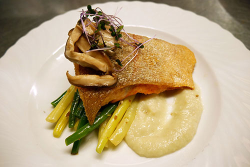 Pan-roasted Hudson Valley Farmed Steelhead Salmon with sweet and sour eggplant mash, sauteed green beans, and a ground cherry and ginger leaf salsa fresca