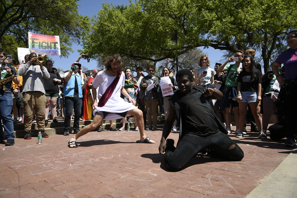Jonathan Clement, 20, dressed as Jesus, dances with Jaye Douglas, a UNT freshman, during a protest.