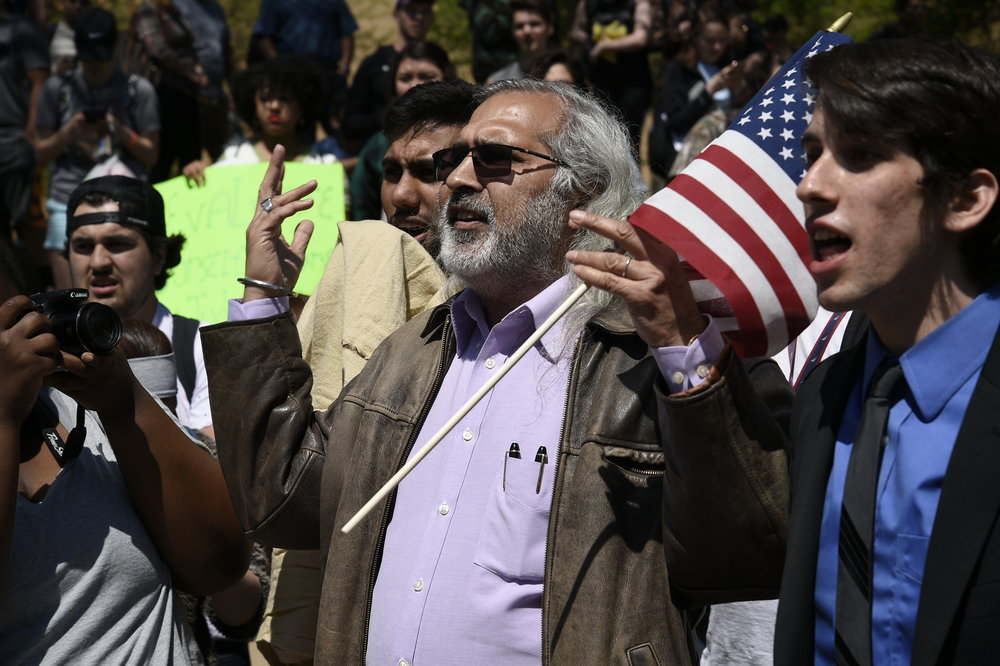 UNT professor Masood Raja debates with street preacher at a protest.