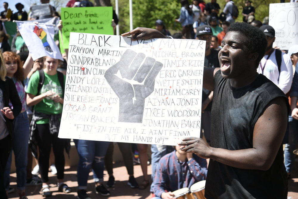 Jaye Douglas, a freshman at UNT, holds up a sign and calls for action.