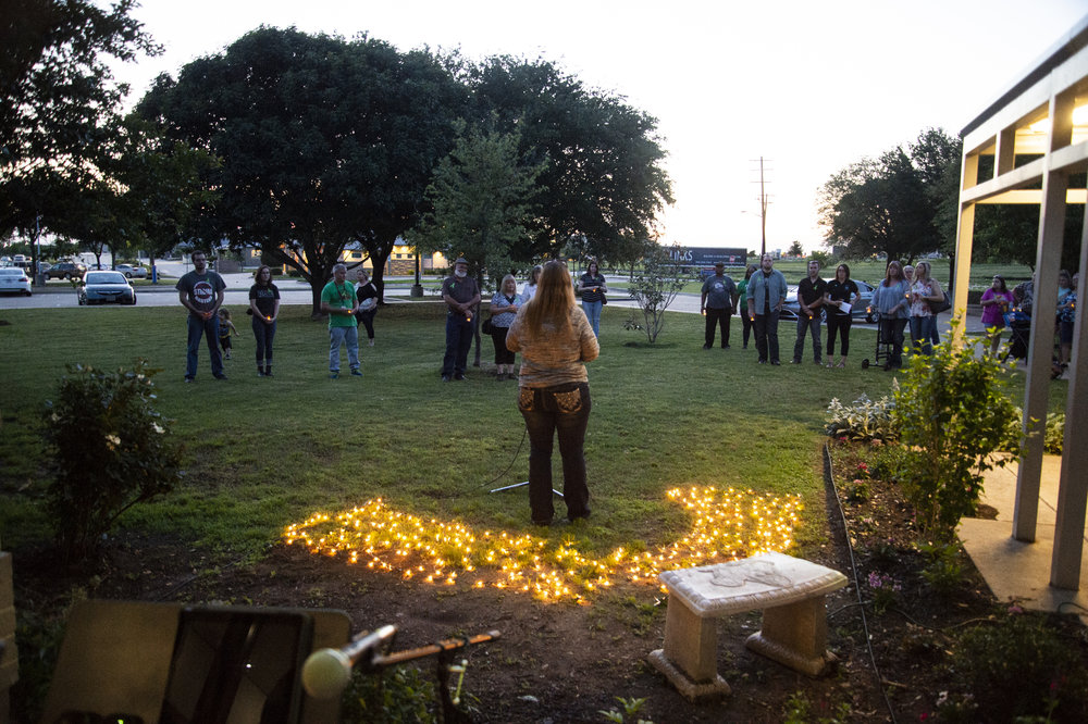 Tammy Weppelman speaks to a crowd outside Denton County MHMR on Sunday during the organization's third annual candlelight vigil. Weppelman is the organization's Administrator of Special Projects.