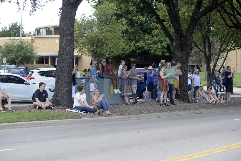 Denton residents sit along the curb near the Denton Civic Center across the street from Backyard on Bell. When the bar/venue filled to capacity during a town hall event for Senate candidate Beto O'Rourke, locals were forced to find adjacent areas to listen to the rally. Jake King/DRC