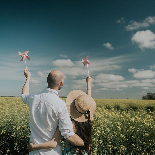 A lovely couple with a pinwheel at a Canola Field in Geelong