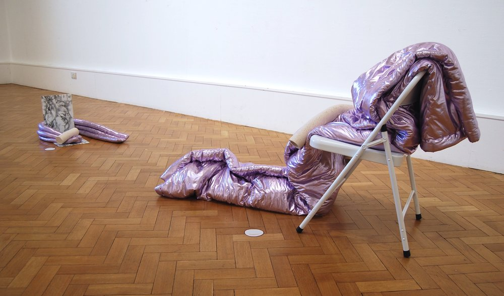 "Same, same but different, different, so let's move in together – Brugge / London   – metallic lavender PVC, wadding and extruded clay on white Habitat chair with vinyl cut-out / metallic lavender PVC, stuffing and extruded clay on 'marmi' self-adhesive film, packing tape and card with vinyl cut-out, 2017       Shown at ' Graffiti Check',  group show at Sassoon Gallery, Folkestone in January 2017 and at  'Queer Art(ists) Now'  group show at Archive Gallery, Haggerston, London, 12th -15th October, 2017, part of  'And What? Queer. Arts. Festival.'  2017   ""Arranged in conversation with itself, the work is about queer cohabitation; the discussion, decision and continual renegotiation of the desire to live together. The materials used in the work combine objects and motifs that reference both the memories of time spent away together, along with hopeful future furnishing decisions."""