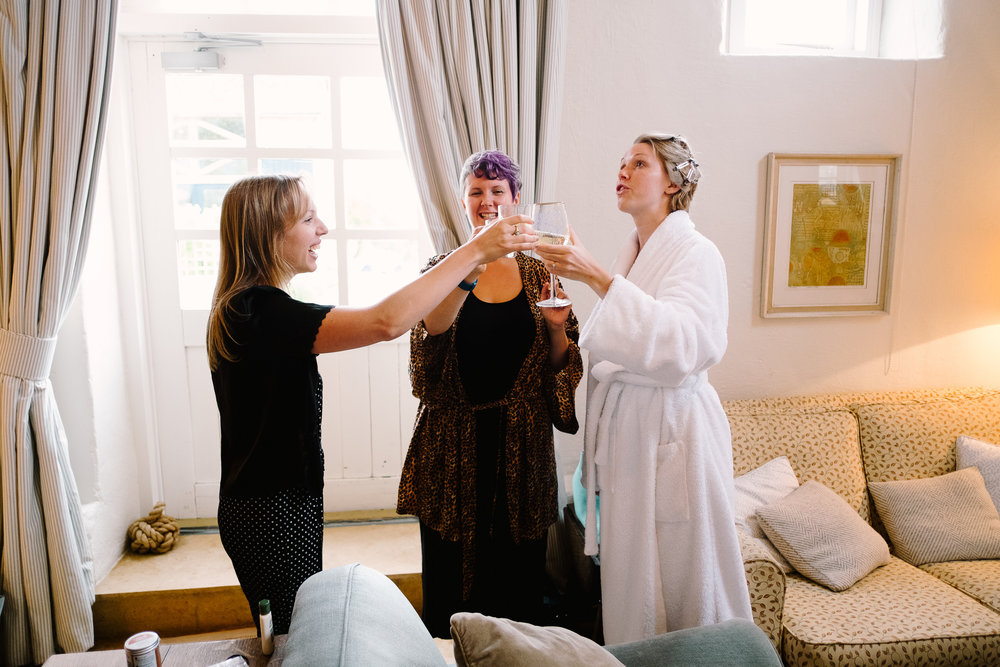 A bride and bridemaids drinking champagne at Merriscourt Wedding Venue, Oxfordshire